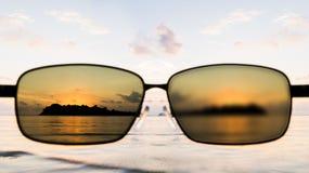 Puesta del sol en el mar con las gafas de sol Imagen de archivo