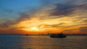 Puesta del sol en el mar con las siluetas Fotografía de archivo libre de regalías