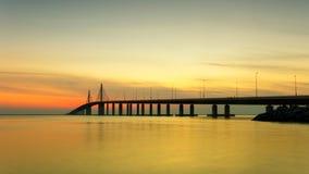 Puesta del sol en el mar con el puente sobre el panorama pacífico del agua Foto de archivo libre de regalías
