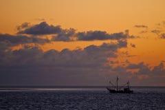 Puesta del sol en el mar con un barco de pesca en el frente imagen de archivo