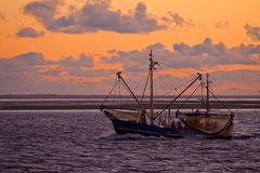 Puesta del sol en el mar con un barco de pesca en el frente imagenes de archivo