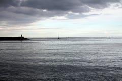 Puesta del sol en el mar con un rompeolas hecho de rocas Imágenes de archivo libres de regalías