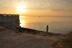 Puesta del sol en el mar de Azov, muchacha en la orilla Fotos de archivo libres de regalías