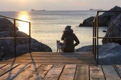 Puesta del sol en el mar Puesta del sol de observación de la muchacha y del gato Foto de archivo