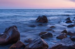 Puesta del sol en el mar. En cantos rodados grandes del primero plano. Fotos de archivo