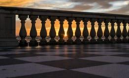 Puesta del sol en el mar entre la columna Imagenes de archivo