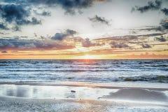 Puesta del sol en el mar tempestuoso Imágenes de archivo libres de regalías