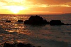 Puesta del sol en el océano con las rocas en Tailandia Imagen de archivo libre de regalías