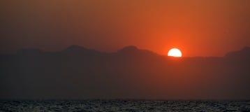 Puesta del sol en el océano con las siluetas de las montañas Imagenes de archivo