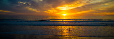 Puesta del sol en el océano con las siluetas de personas que practica surf Imagen de archivo