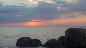 Puesta del sol en el océano con los cantos rodados en frente metrajes