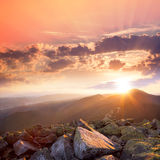 Puesta del sol en el paisaje de las montañas Cielo dramático, piedra colorida Fotos de archivo libres de regalías