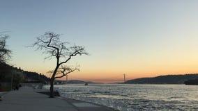 Puesta del sol en el puente de Bosphorus de la costa costa de Bosphorus y del puente de los m?rtires del 15 de julio almacen de metraje de vídeo