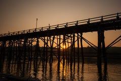 Puesta del sol en el puente de madera más largo y la ciudad flotante de Sangkla Fotos de archivo libres de regalías