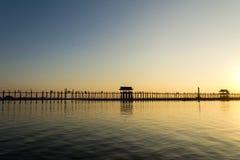 Puesta del sol en el puente del Teakwood de U Bein, Amarapura en Myanmar (Burmar Imagen de archivo