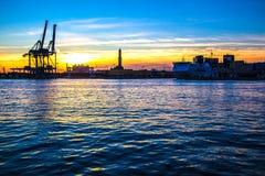 Puesta del sol en el puerto del ` s de Génova, silueta del Lanterna, Italia Imagen de archivo libre de regalías
