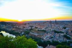 Puesta del sol en el puesto de observación de Toledo, España Río de Tajo alrededor de la ciudad y el Alcazar y catedral en el fon foto de archivo