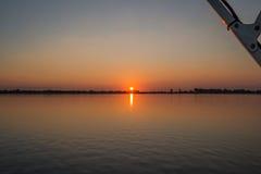 Puesta del sol en el río con el puntal en esquina fotografía de archivo libre de regalías