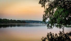 Puesta del sol en el río con la reflexión del árbol Fotos de archivo libres de regalías