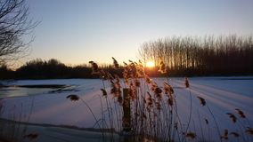 Puesta del sol en el río congelado Fotografía de archivo libre de regalías