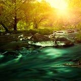 Puesta del sol en el río de la montaña Foto de archivo