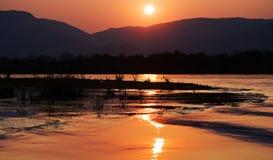 Puesta del sol en el río Zambezi África Frontera de Zambia y de Zimbabwe Imagen de archivo libre de regalías