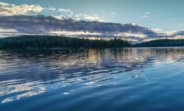 Puesta del sol en el sol del lago Ladoga detrás de las nubes reflexión Fotos de archivo