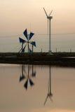 Puesta del sol en el uso antiguo y nuevo del molino de viento para el movimiento la agua de mar i Fotos de archivo libres de regalías
