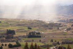 Puesta del sol en el valle debajo de las montañas Foto de archivo libre de regalías