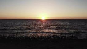Puesta del sol en horizonte con las ondas del mar que golpean la orilla del banco de mar Sunroad durante puesta del sol con las o almacen de video