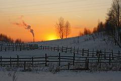 Puesta del sol en invierno con la chimenea en horizonte Fotos de archivo