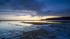 Puesta del sol en la bahía de Kimmeridge, Dorset foto de archivo