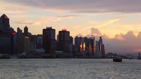 Puesta del sol en la bahía de Kowloon con el transbordador en el puerto de Hong Kong, fondo del paisaje urbano almacen de metraje de vídeo