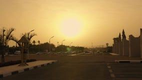 Puesta del sol en la calle con las palmeras crecientes Sol grande almacen de metraje de vídeo