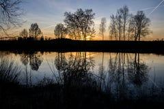Puesta del sol en la charca Bachracek con los árboles imagen de archivo
