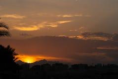 Puesta del sol en la ciudad de Hurghada con los edificios y la silueta de las montañas Imágenes de archivo libres de regalías