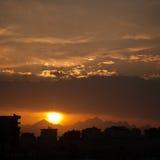 Puesta del sol en la ciudad de Hurghada con los edificios y la silueta de las montañas Fotografía de archivo libre de regalías