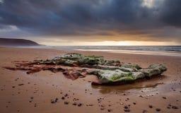 Puesta del sol en la costa atlántica que pasa por alto un canto rodado hermoso enorme debajo de las nubes de tormenta Foto de archivo
