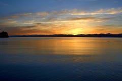 Puesta del sol en la costa del mar Fotos de archivo
