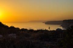 Puesta del sol en la costa mediterránea que pasa por alto el Dliffs y el th Fotos de archivo libres de regalías