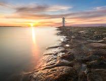 Puesta del sol en la costa, molino de viento del faro en Swinoujscie, Polonia Fotografía de archivo