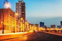 Puesta del sol en La Habana vieja con las luces de calle del EL Malecon Fotos de archivo libres de regalías