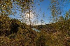Puesta del sol en la mina o lago o charca con la playa arenosa, agua verde, Fotografía de archivo libre de regalías