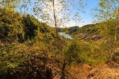 Puesta del sol en la mina o lago o charca con la playa arenosa, agua verde, Fotografía de archivo