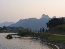 Puesta del sol en la orilla con el fondo de la montaña, viaje en Vang VI Imagenes de archivo
