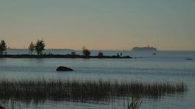 Puesta del sol en la orilla de la bahía Vista de la nave que entra en el puerto metrajes