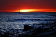 Puesta del sol en la orilla de mar imagenes de archivo