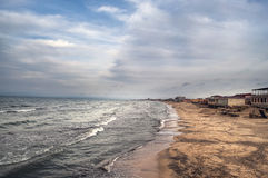 Puesta del sol en la orilla de mar de una playa con las rocas y las ondas tempestuosas, paisaje marino hermoso en el mar Caspio A foto de archivo
