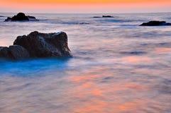 Puesta del sol en la orilla de mar rocosa Imagenes de archivo