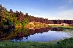 Puesta del sol en la orilla de un pequeño río Fotografía de archivo